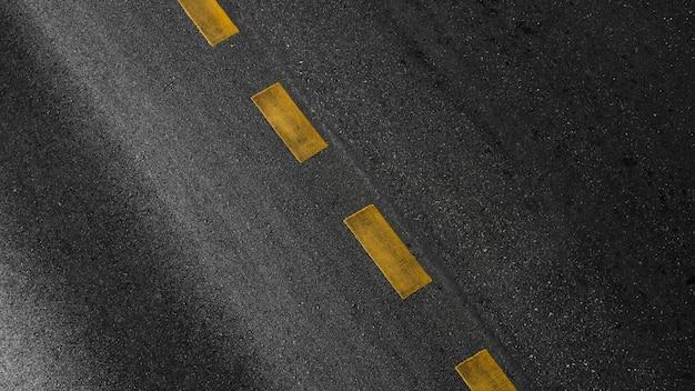 Gele verflijn op zwart asfalt. ruimtevaart achtergrond