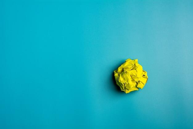Gele verfrommelde vellen papier op blauwe achtergrond. - ruimte voor uw tekst.