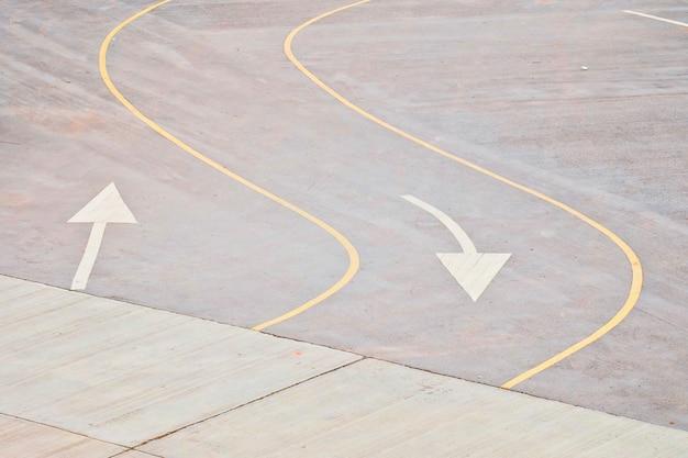 Gele verkeers gebogen lijnen en wit pijlsymbool op de weg