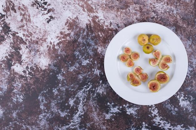 Gele vijgen met rode zaden in een witte plaat.