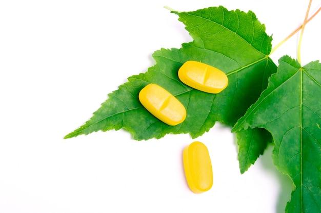Gele vitaminepillen over groene bladeren op witte achtergrond