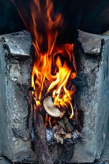 Gele vlam op het houtblok in de oven.