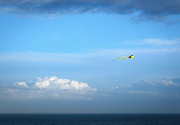 Gele vlieger tegen een blauwe lucht met een paar wolken boven de sea dover uk