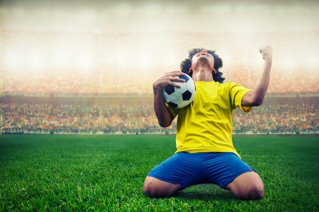 Gele voetbalvoetballer die zijn doel in het stadion viert
