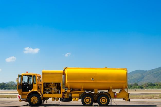Gele vrachtwagen met brandstoftank op baan