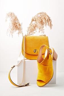 Gele vrouwelijke mode-accessoires, schoenen, zonnebril en handtas.