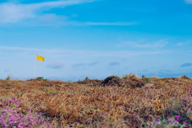 Gele waarschuwingsvlag op een strand tegen de blauwe hemelachtergrond.