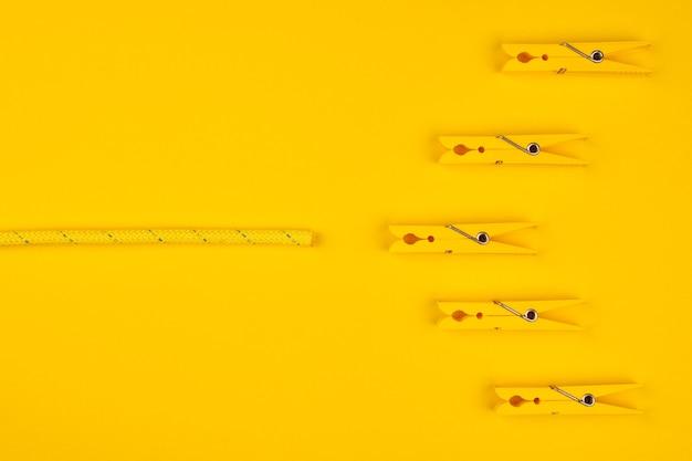 Gele wasknijpers en touw. vang je geluk. gele achtergrond. gelukkig pauzeconcept.