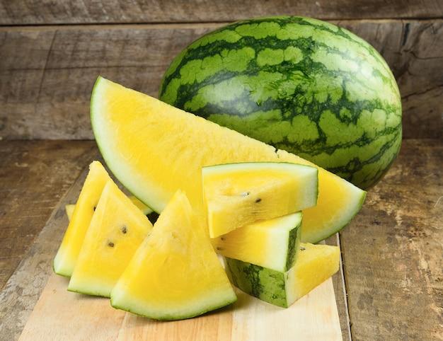 Gele watermeloen die op houten lijst wordt gesneden