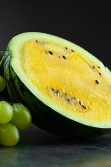 Gele watermeloen met druiven.
