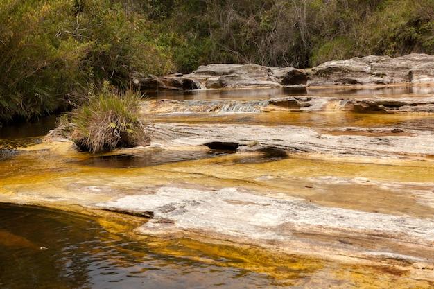 Gele waterrivier op kwartsietrotsen