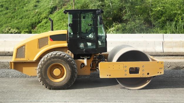 Gele wegwals bij wegenbouw en aard