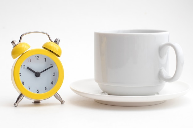 Gele wekker en een witte kop koffie.