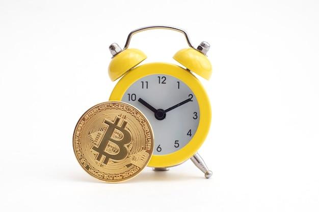 Gele wekker en gouden bitcoin-munt. een goed moment om een cryptovaluta te verdienen en te delven