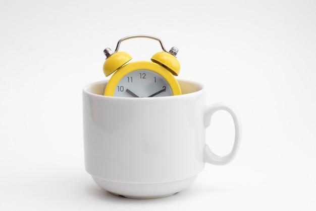Gele wekker in witte kop voor koffie. vroeg in de ochtend.