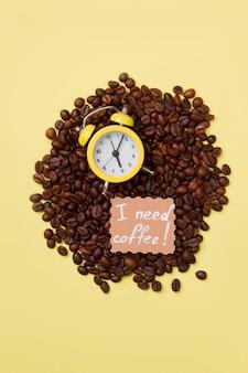 Gele wekker op een hoop koffiebonen. ik heb koffie nodig. zes uur of uur.