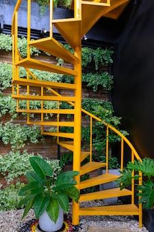 Gele wenteltrap met planten op bakstenen muur