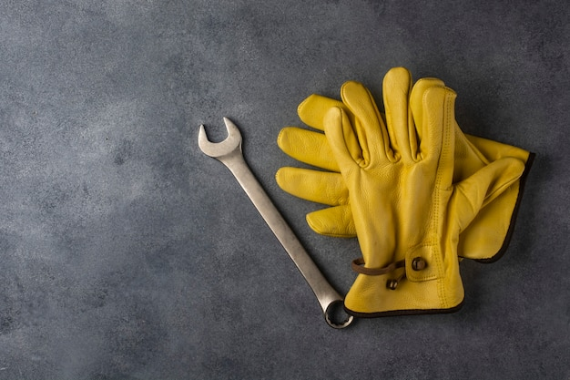 Gele werkhandschoenen en een moersleutel op de betonnen vloer