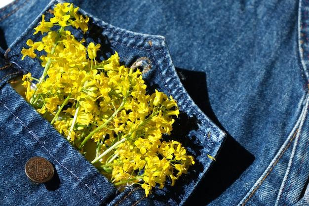 Gele wilde bloemen in een spijkerjasje, kopieerruimte in de zomerstemming