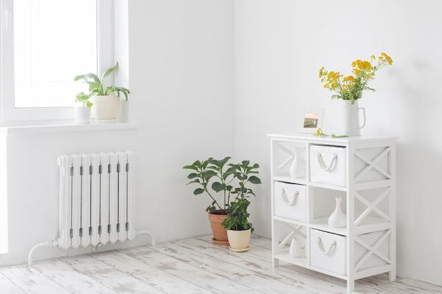 Gele wilde zomerbloemen in kruik op wit vintage interieur