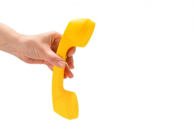 Gele zaktelefoon in vrouwenhand die op wit wordt geïsoleerd.