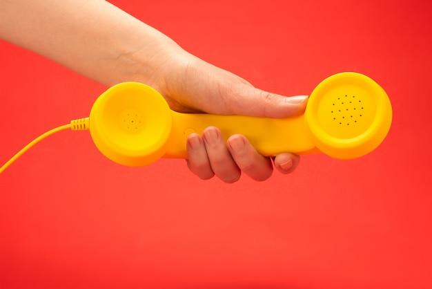 Gele zaktelefoon op een rode achtergrond in vrouwenhand.