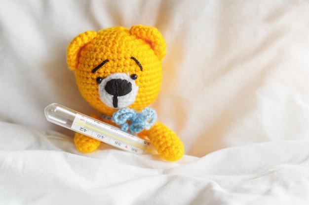 Gele zieke teddybeer met thermometer in witte slaapkamer.