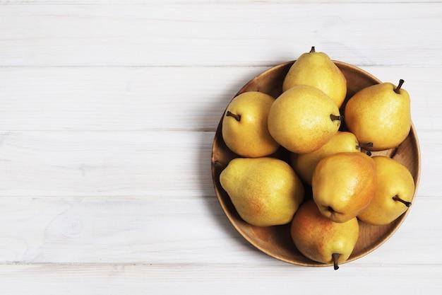 Gele zoete peren op een witte houten achtergrond. ruimte kopiëren. ontwerp elementen.