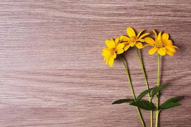 Gele zomerbloemen op een houten achtergrond. heldere bloemensamenstelling. ruimte voor tekst. groene stengels op een bruine tafel. sjabloon voor wenskaart.
