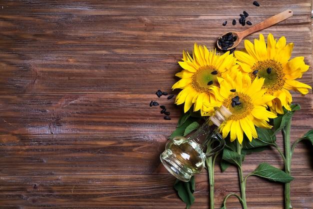 Gele zonnebloemen met olieglasfles op achtergrond van oude omheining.