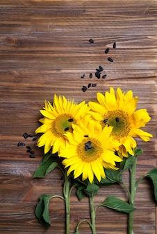 Gele zonnebloemen op achtergrond van oude omheining.