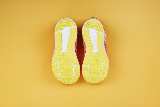 Gele zool van een sneaker op een gele achtergrond. minimalistisch concept, sportstijl, bovenaanzicht