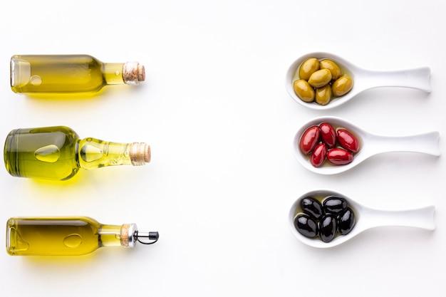 Gele zwarte rode olijven in lepels met bladeren en olieflessen
