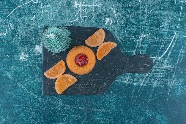 Gelei gevulde cake, marmelades en een boombeeldje op een zwart bord op blauwe achtergrond. hoge kwaliteit foto
