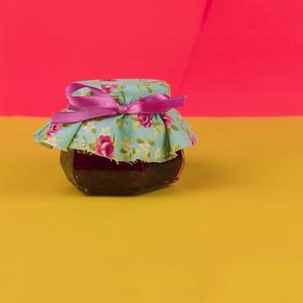 Gelei in op pot geïsoleerd op gekleurde achtergrond. pasteltrend in frisse kleuren. ruimte voor tekst