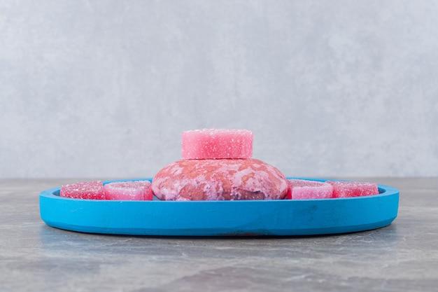 Gelei-snoepjes en een koekje gerangschikt op een schaal op een marmeren oppervlak