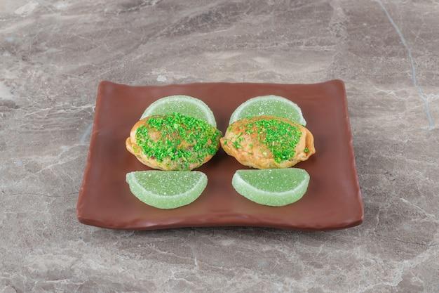 Gelei-snoepjes en kleine broodjes met groene topping op een schotel op marmeren ondergrond