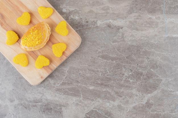Gelei-snoepjes rond een klein broodje met citroensmaakpoeder op een marmeren oppervlak