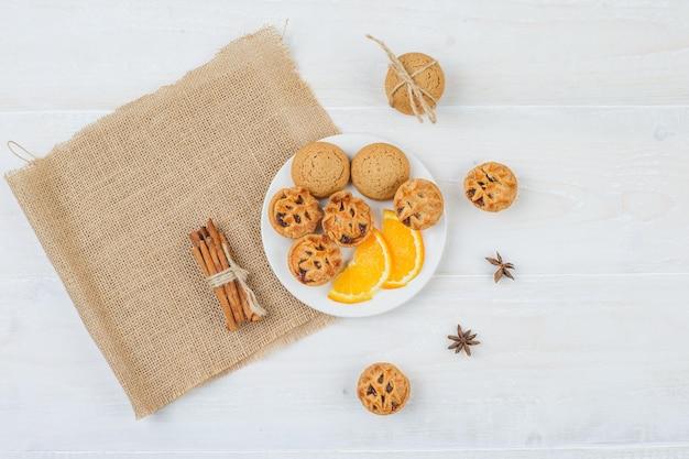 Gelei vullende taarten, koekjes en sinaasappel in een bord met kaneel en een placemat