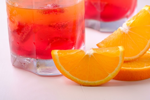 Geleidessert met aardbeien in drankglas met oranje plakken