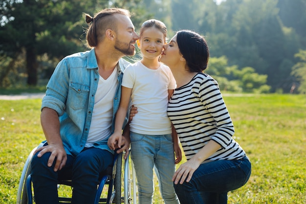 Geliefd kind. zachte jonge moeder en liefhebbende vader met een handicap, zittend in een rolstoel, hun dochtertje op beide wangen kussen
