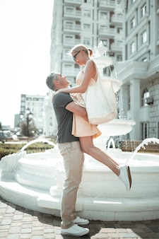 Geliefd voelen. gelukkig sterke man die zijn lachende mooie vrouw in zijn armen neemt tijdens hun wandeling.