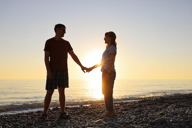 Geliefden glimlachen en kijken elkaar aan in de stralen van de ondergaande zon aan de kust
