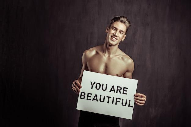 Geloof in jezelf. gelukkig aardige jonge man lacht naar je terwijl je tegen een donkere muur staat
