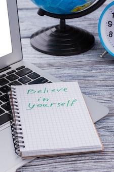 Geloof in jezelf notitie liggend op een laptop pc. dromen en reizen concept.