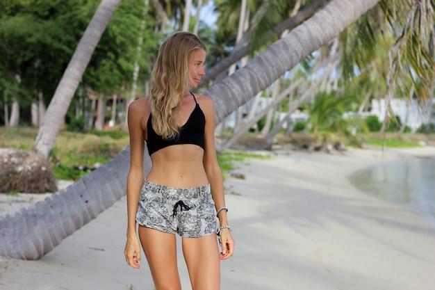 Gelooid fit slank kaukasisch model op palmboom op tropisch strand