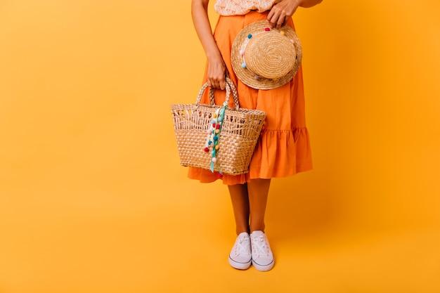 Gelooid meisje in oranje rok en witte schoenen die zich op geel bevinden. spectaculair vrouwelijk model met trendy hoed poseren in studio.