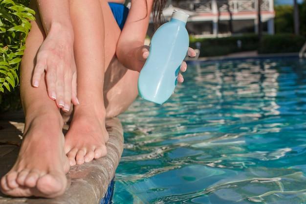 Gelooid vrouwelijk benen dichtbij zwembad met zonnescherm