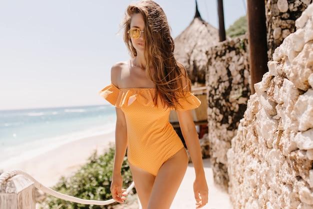 Gelooid wit meisje in elegante romper poseren in exotische resort. outdoor portret van geweldige brunette vrouw draagt oranje zwembroek weekend doorbrengen in de buurt van zee.