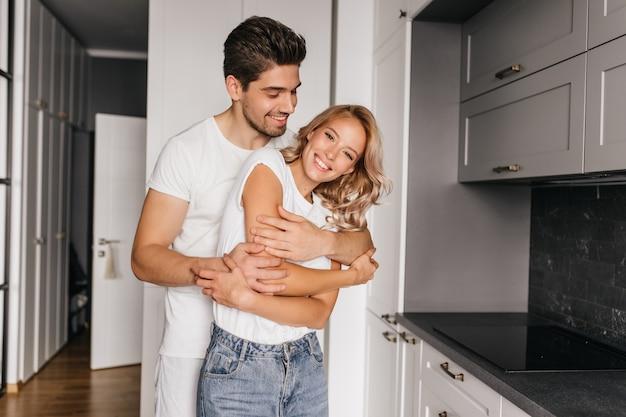 Gelooide lachende man dansen met vrouw. indoor portret van paar omarmen in gezellig appartement.
